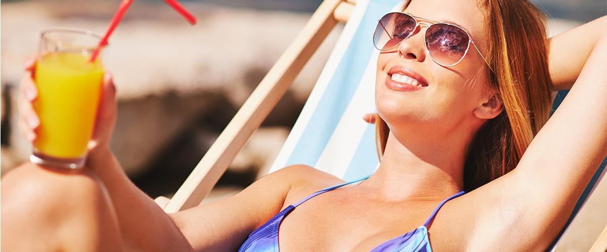 リラックスして笑う日光浴中の女性