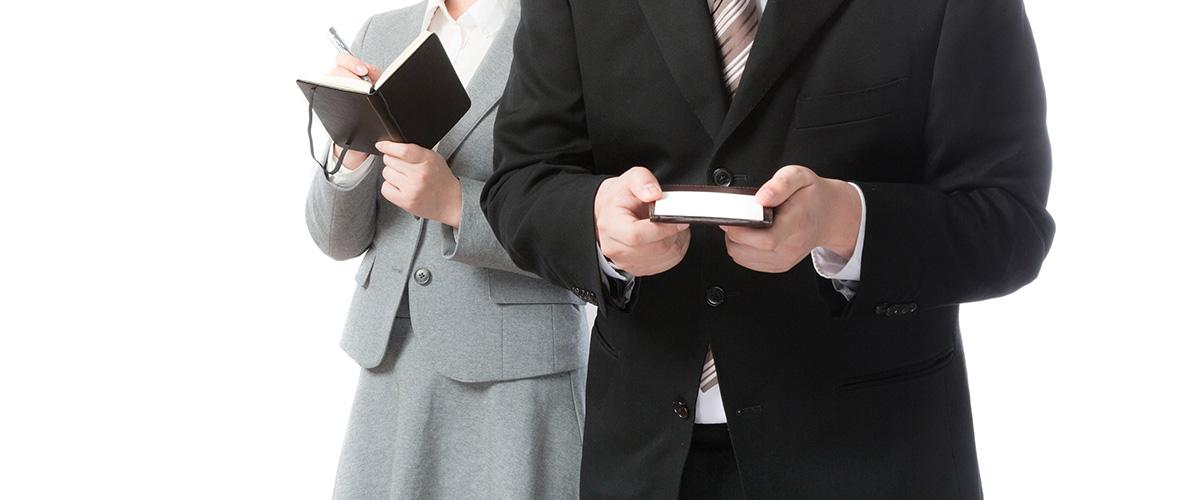 名刺を持ったビジネスマンと手帳を持つビジネスウーマン